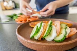 Op een bord liggen de gesneden komkommer, tomaat en mozzarella.