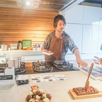 De chocolatier staat aan het gasfornuis terwijl hij een uitleg geeft over het maken van praline's.