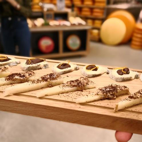 Op een houten presenteerplank worden twee verschillende hapjes kaas met chocolade gepresenteerd.
