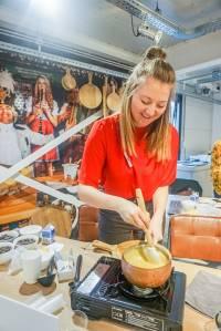 De foodblogger roert in een fondue pot de vanille ganache goed door elkaar.