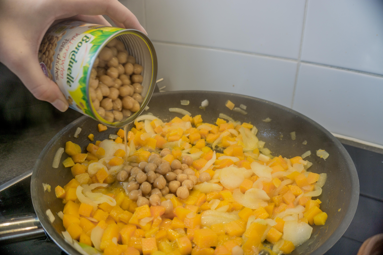 Meng in een pan de pompoen stukjes met de ajuin en kikkererwten.