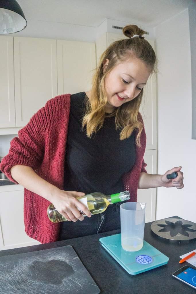 Op een keukenweegschaal staat een maatbeker waarin witte wijn wordt afgemeten.