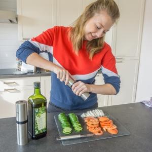De gesneden tomaat, komkommer en mozzarella worden gekruid met peper en zout.