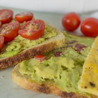 Twee toasten liggen op elkaar. Beide zijn belegd met guacamole.