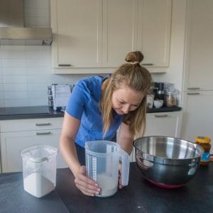Een vrouw meet in de keuken de hoeveelheid bloem af, alvorens toe te voegen aan het eimengsel.