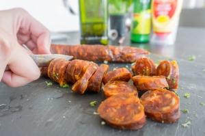 Chorizo wordt in stukjes gesneden.