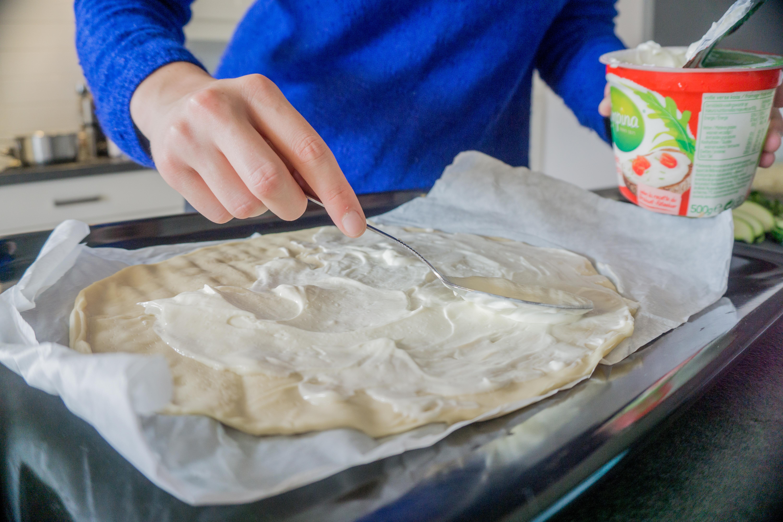 Smeer het pizzadeeg in met platte kaas.