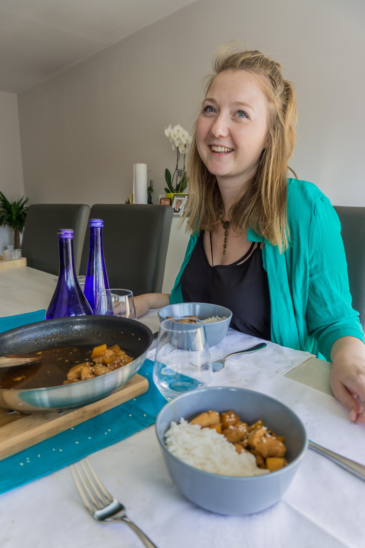 Vrouw zit aan tafel met het gerecht kip zoetzuur op tafel.