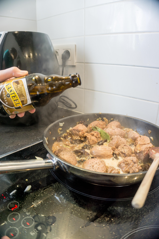 Een pan met reeragout en gedroogde pruimen wordt geblust met een donker kasteel bier.