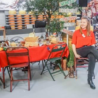 Naast een gedekte tafel met rood tafelkleed en kaasspullen zit de foodblogger op de stoel.