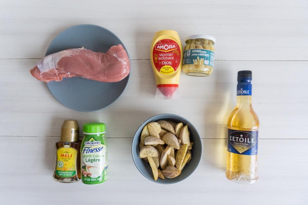 Op een witte ondergrond worden alle ingrediënten voor het recept varkenshaas met asperges getoond.