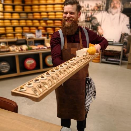 De chefkok presenteert op een houten serveerplank de aperitief hapjes.