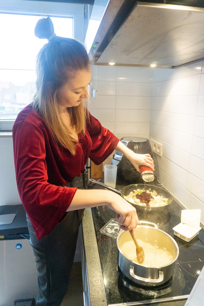 Op het vuur staan twee pannen. In de éne zit risotto en in de andere pan selder met spinazie, kip en bonen.