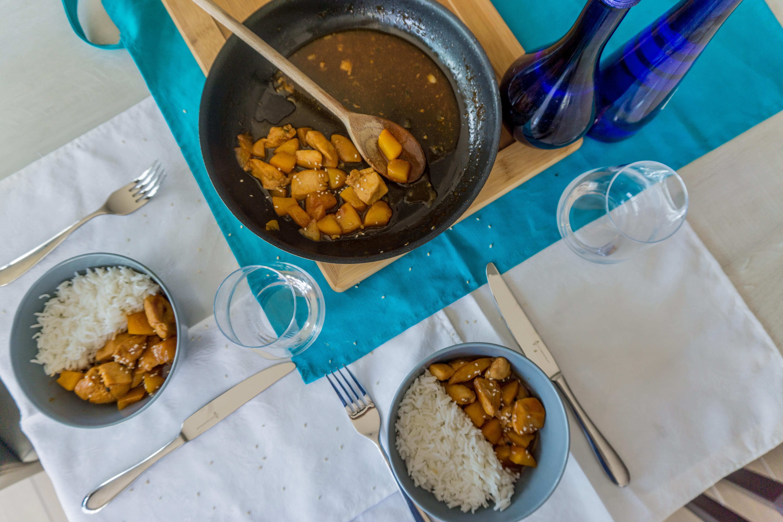 Op een gedekte tafel staan twee kommetjes gevuld met rijst en kip zoetzuur.