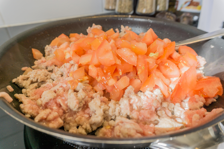 In een pan wordt gehakt en tomaat gebakken.
