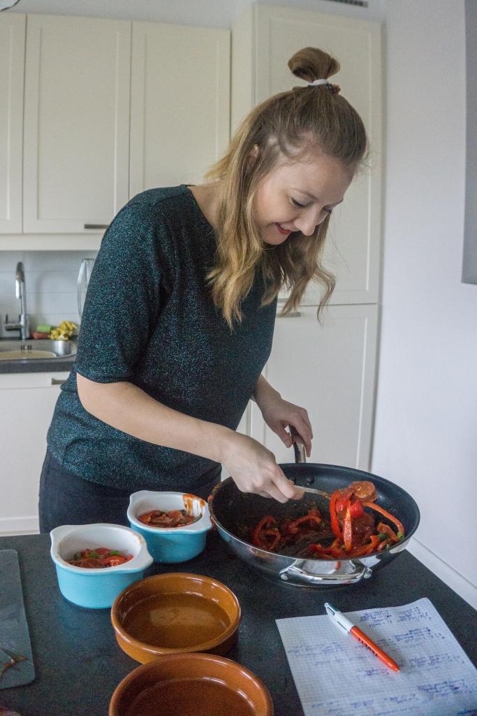 Uit een kookpan wordt het groentenmengsel van tomaat, paprika, lente-ui en chorizo verdeeld over twee kleine ovenschaaltjes.