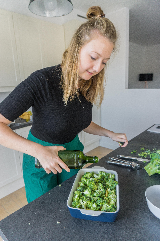 Vrouw kapt olijfolie over ovenschotel.