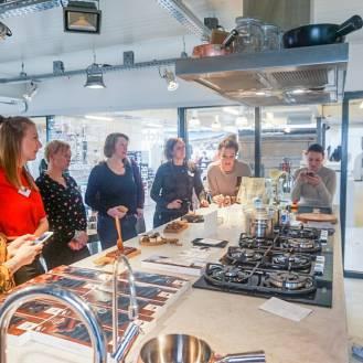 Een groep foodbloggers staan rond een kookeiland met marmeren blad voor een workshop bonbons maken.