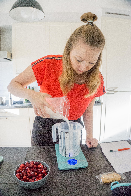 Op een blauwe keukenweegschaal wordt suiker afgewogen in een doorzichtige maatbeker.