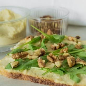 Een toast met hummus, rucola en walnoten.