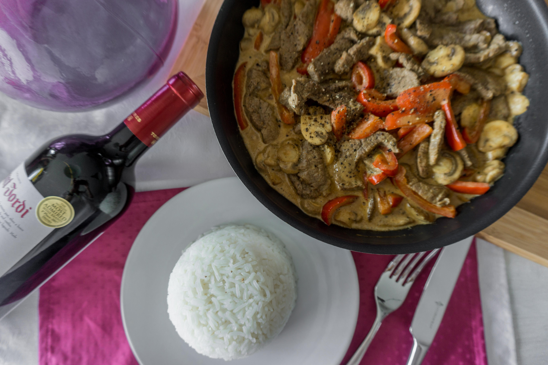 een pan met runderreepjes stroganoff staat op tafel naast een bord met rijst.