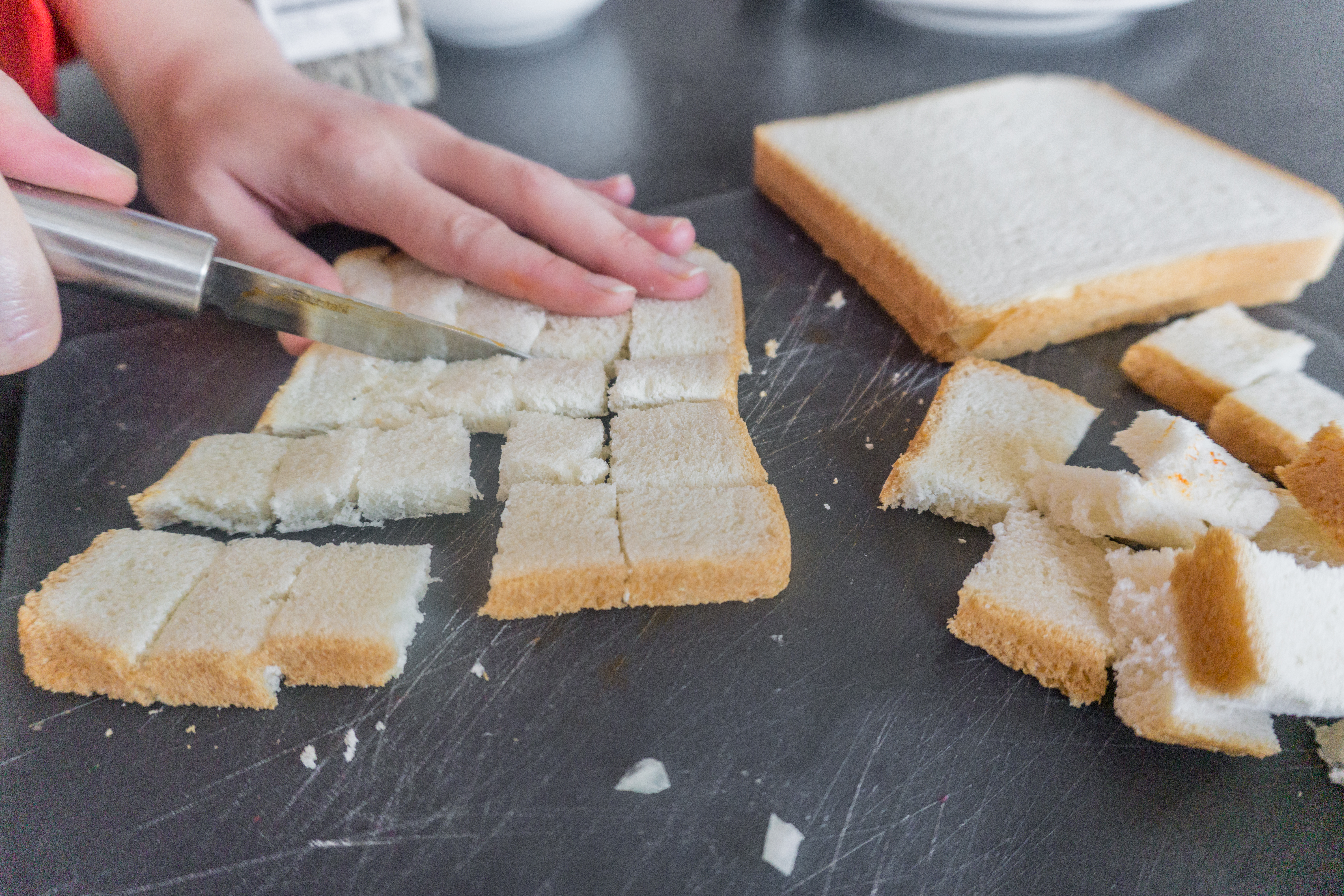 The bread is being cut into smaller pieces for the salad.