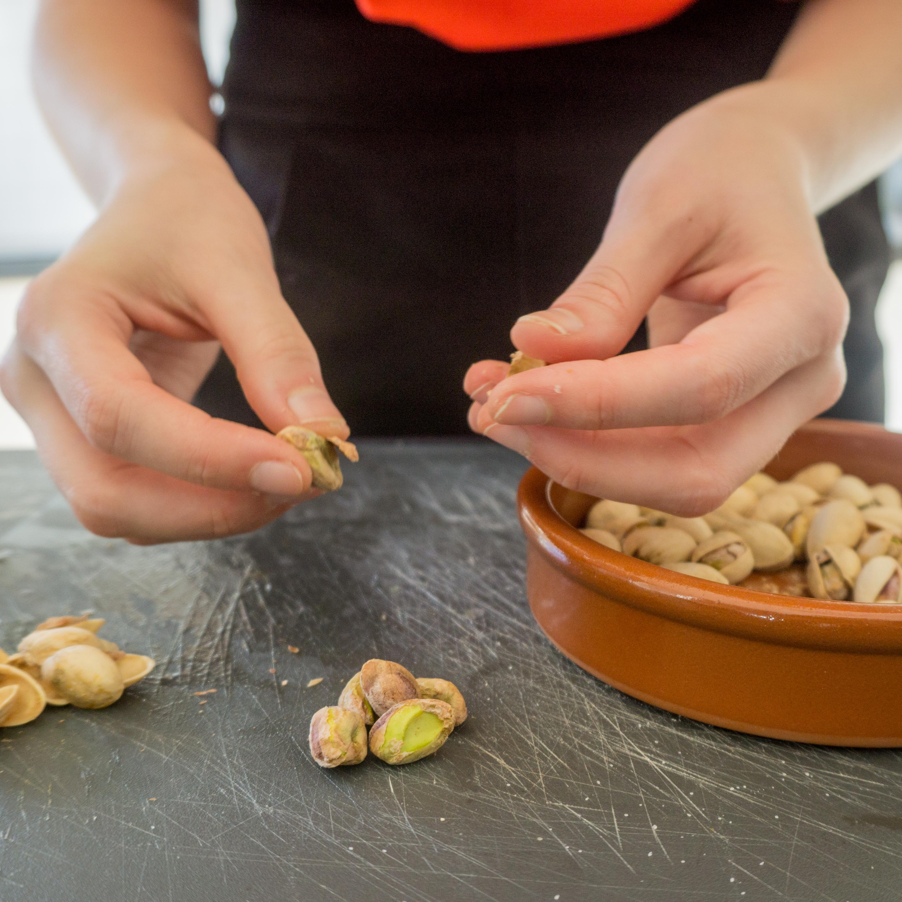 De pistachenoten worden gepeld vanuit een bruine kom.