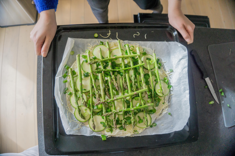 De platboordpizza met asperges ligt klaar op een ovenschaal en wordt in de oven geplaatst.
