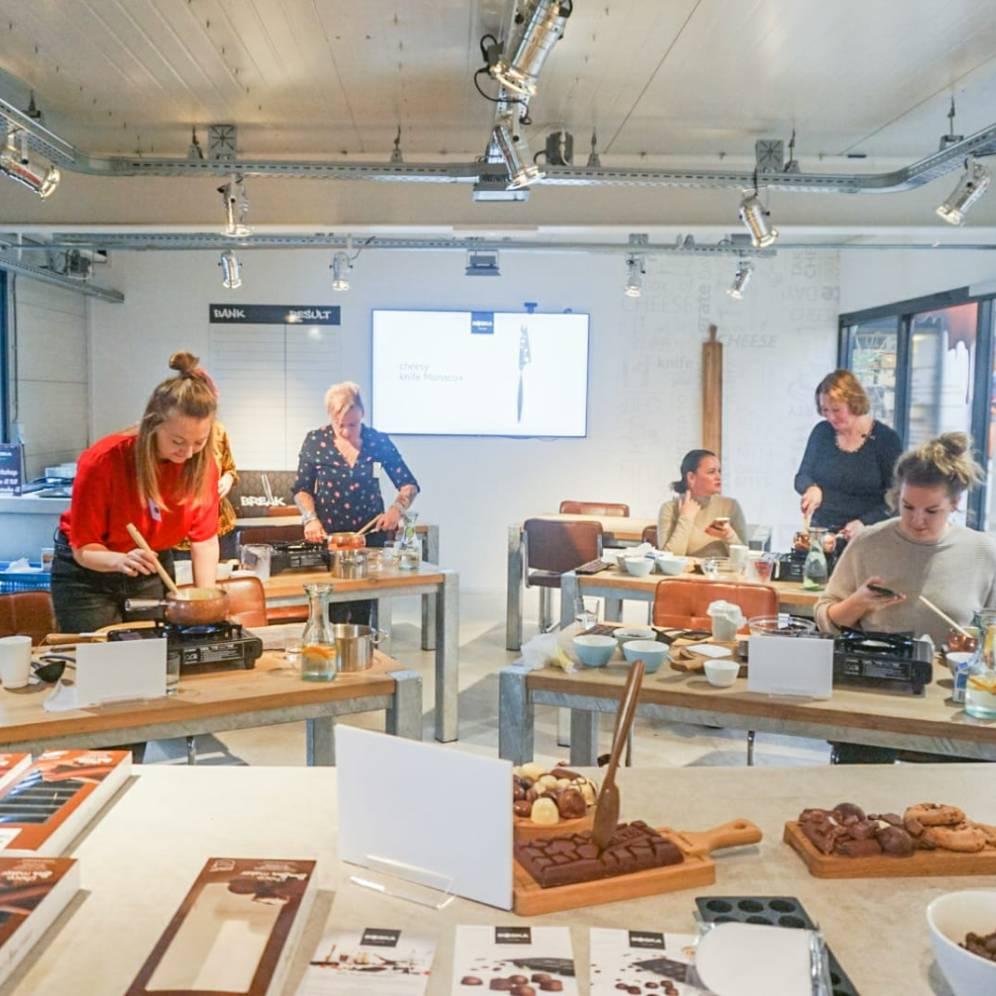 Zes tafels per twee staan in een ruimte waar foodblogger zelf bonbons aan maken.