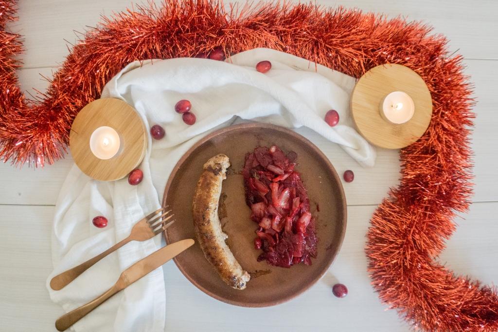 Op een kleisteen bord ligt een worst met daarnaast een rode bieten salade. Rondom het bord ligt er kerst versiering en enkele veenbessen.