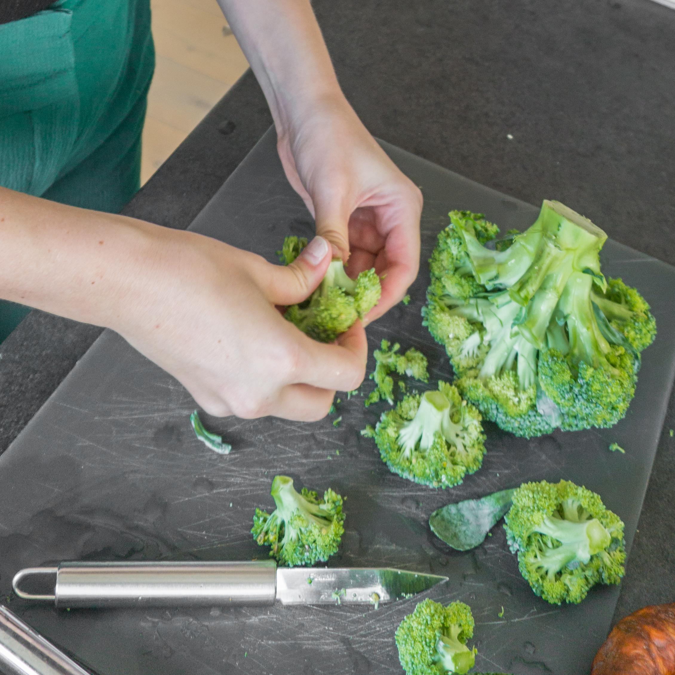 Broccoli wordt in stukjes gesneden.