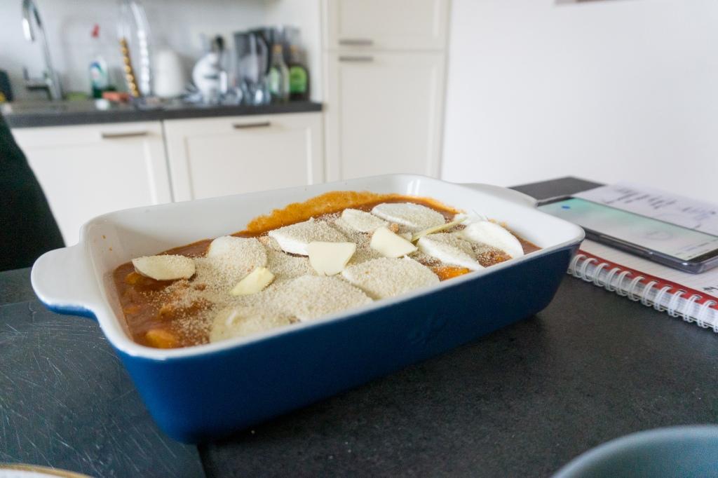 Een blauwe ovenschotel met bolognese saus, kip en mozzarella is klaar voor in de oven.